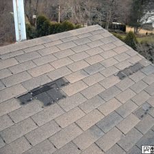 shingles missing from a storm roof damage in Cranston, Rhode Island