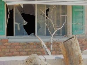 broken windows in a vandalized home